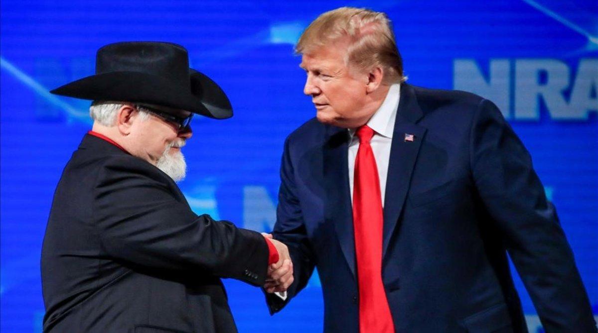 Donald Trump saluda a un asistente a la reunión de la Asociación Nacional del Rifle.
