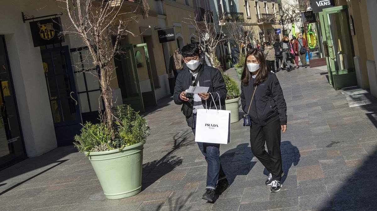 Dos clientes pasean por las tiendas de La Roca Village con mascarillas protectoras por miedo a contraer el coronavirus, este miércoles.