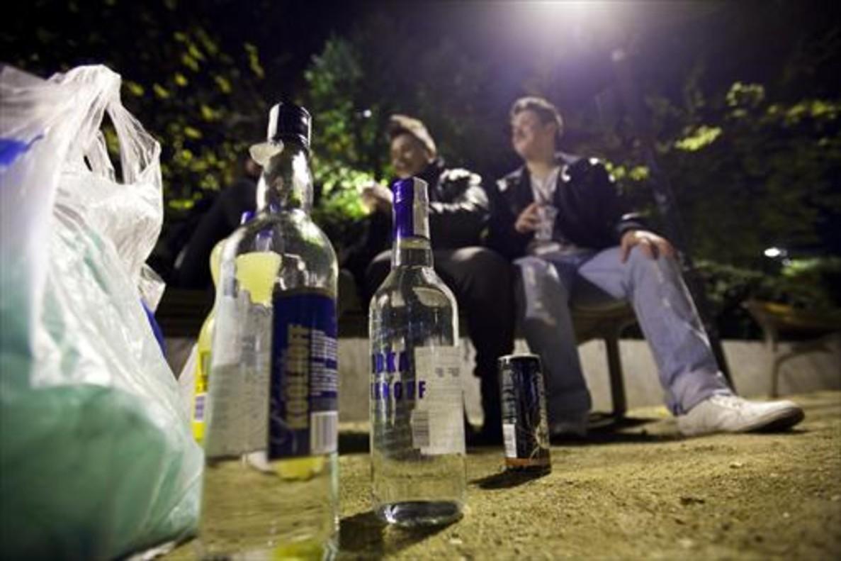 Dos jóvenes beben en un banco público durante un botellón nocturno montado, con alcohol de alta graduación, en la plaza de Letamendi del Eixample de Barcelona.