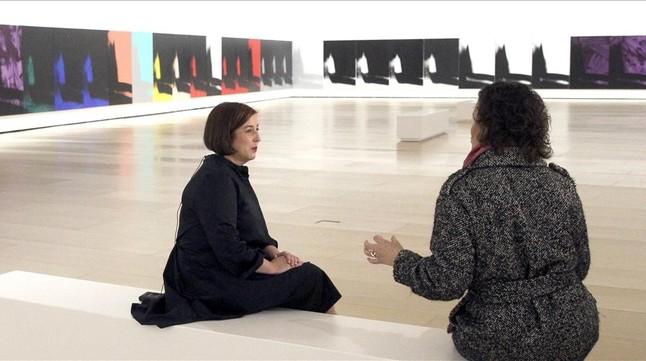Dos mujeres conversan ante algunos de los 102 lienzos de la monumental Sombras de Andy Warhol expuesta en el Guggenheim de Bilbao.