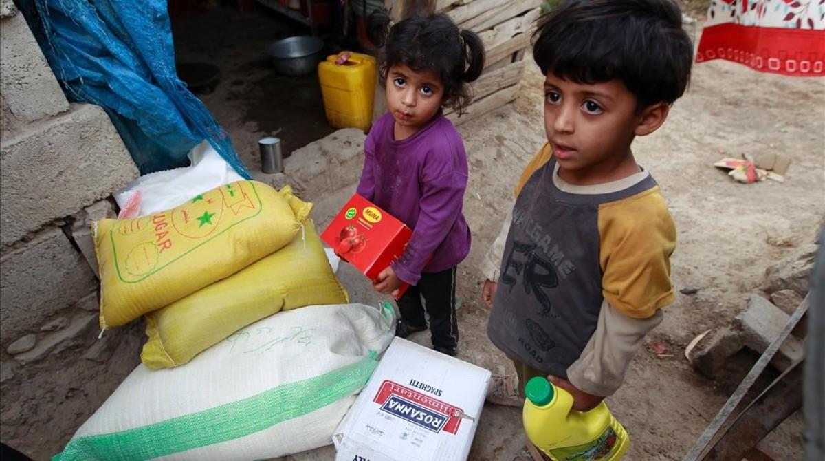 Dos niños yemenís junto a raciones de comida distribuidas por una organización benéfica local, el 15 de junio, en Saná.