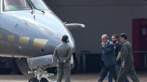Eduardo Cunha camina luego de ser detenido hacia un avion de la Policía Federal.
