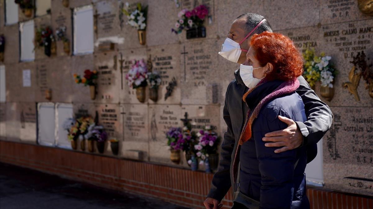 Unos familiares asisten al entierro de una víctima del covid-19.