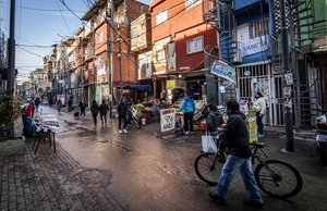 La gente camina por una calle y compra alimentos en los mercados locales en el barrio marginal Barrio 31.