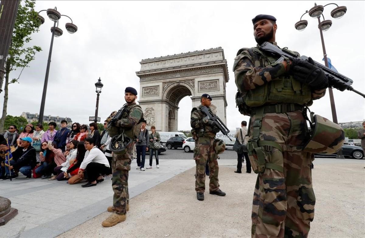 Un grupo de turistas chinos se hacen fotografías, mientrassoldados del ejército patrullan cerca del Arco de Triunfo en París, Francia.