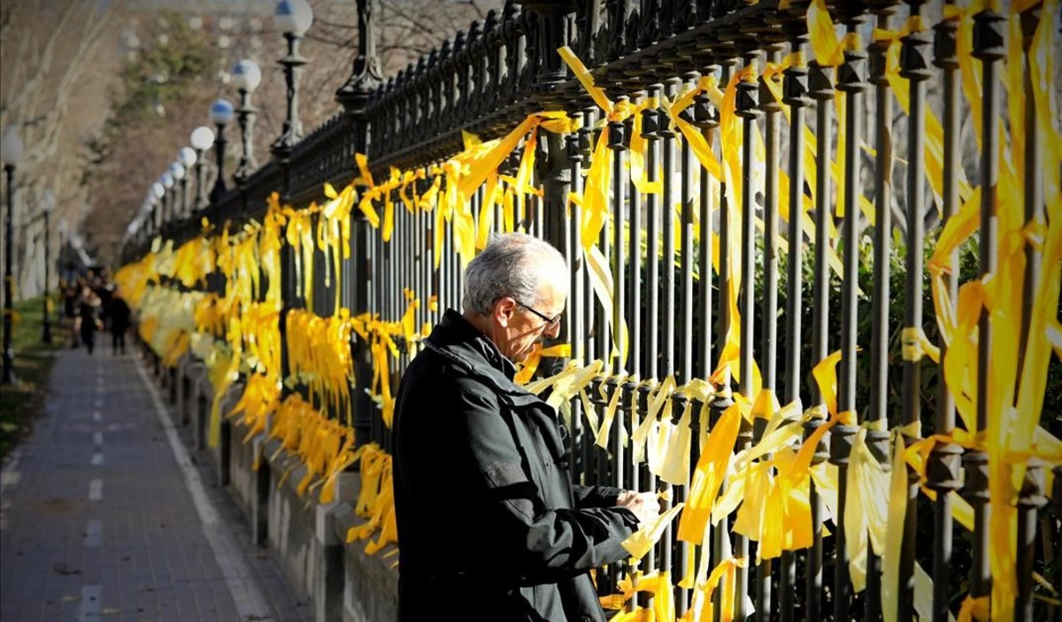 Independentistas colocan lazos amarillos en la verja del parque de la Ciutadella.