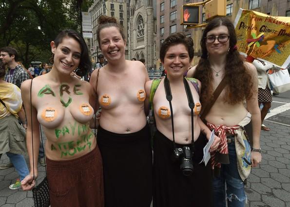Cuatro jóvenes, en toplés y con mensajes pintados en sus cuerpos, en la marcha de Nueva York.