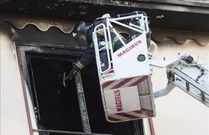 Un bombero revisa desde una autoescalera la vivienda desde la que ha caído la niña.