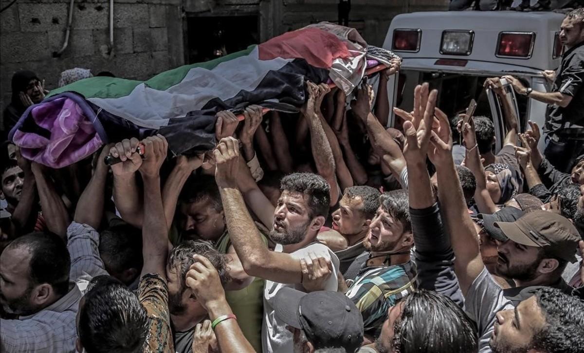 La muchedumbre traslada el féretro de Razan Najjar, la enfermera que ha muerto por los disparos hebreos.