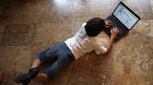 Un niño mira Facebook.