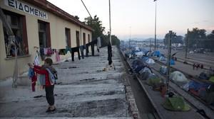 Un niño recoge la ropa tendida en un campo de refugiados situado en la estación de tren de Idomeni.