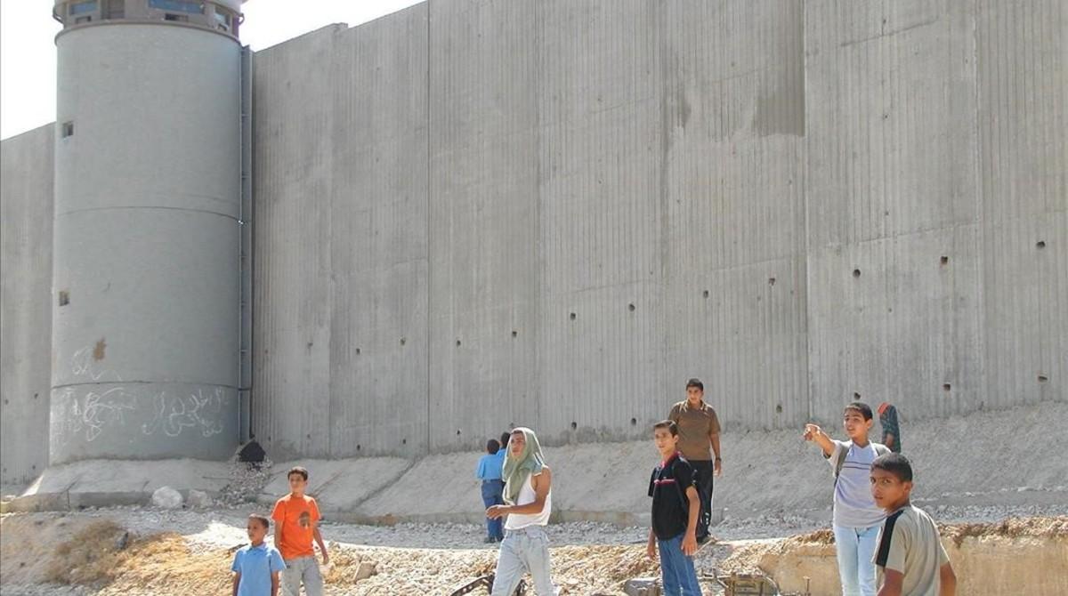 Niños palestinos de camino a la escuela, junto al muro construido por Israel cerca de Qalqilya (Cisjordania).