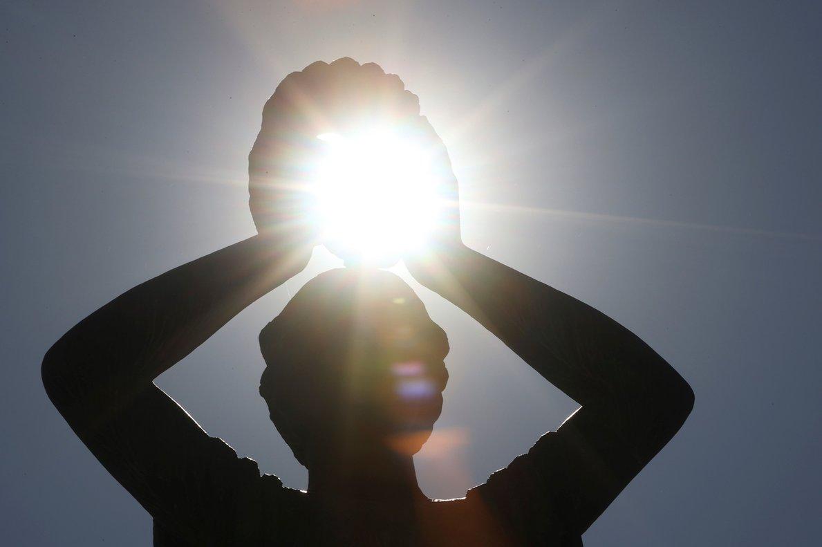 GRAF7860. MADRID, 01/08/2020.- El sol pasa entre las manos de una estatua del madrileño parque de El Retiro. El mes de julio finalizó ayer viernes en plena ola de calor, la primera del año, que ha anotado registros históricos de temperaturas máximas y mínimas, con más de 40 grados en puntos del Cantábrico, noches tropicales en gran parte del país y riesgo extremo de incendios. EFE/ Mariscal