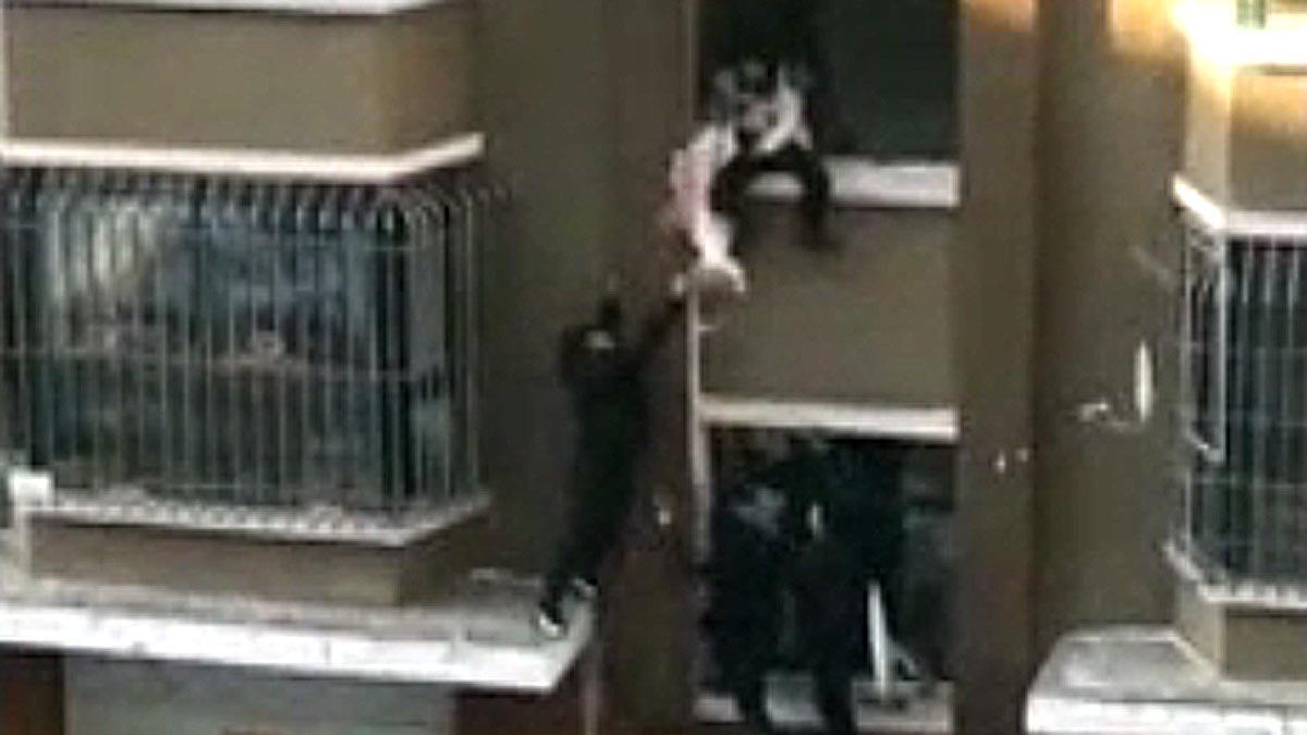 Madre lanza a su bebé de edificio en llamas; lechero lo salva