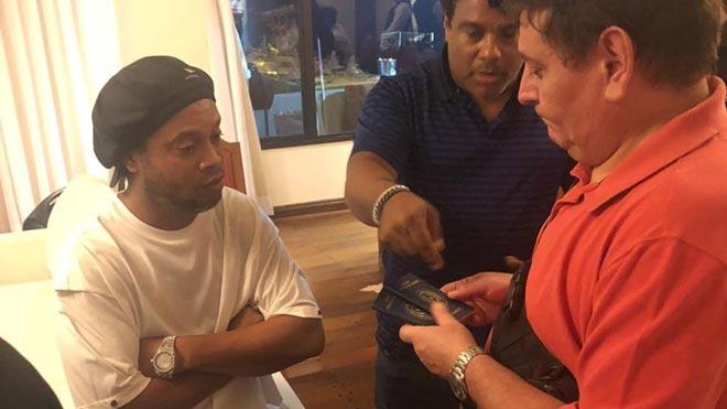 Ronaldinho y su hermano, arrestados por entrar con pasaporte falso a Paraguay. En la foto, las autoridades registran la documentación del futbolista.