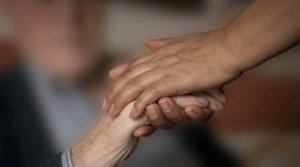 Una mujer coge la mano de una anciana, en una foto de archivo.