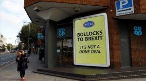 Una mujer pasa al ladode uno de loscarteles anti-Brexit en Londres