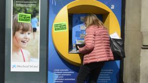 Una mujer saca dinero del cajero automático.
