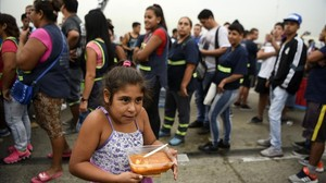 Una niña lleva su ración de comida servida durante una protesta social en Buenos Aires contra la pobreza, el 15 de marzo.