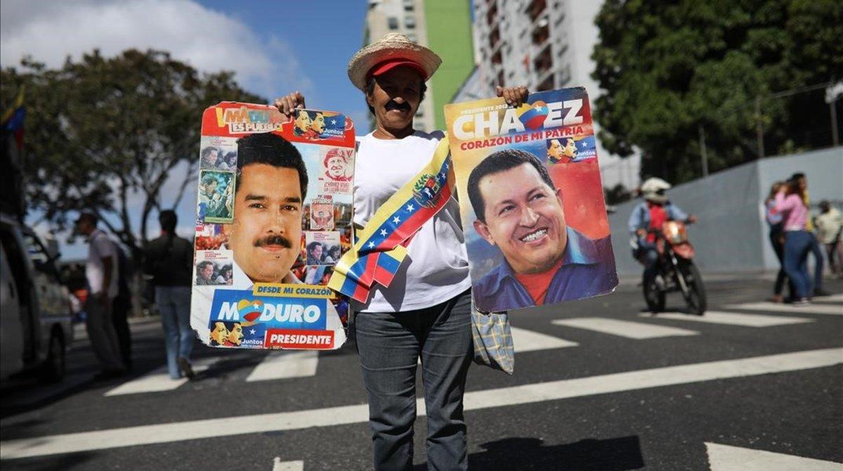 Una simpatizante de Maduro sostiene un cartel del mandatario y otro de Hugo Chávezen una manifestación en Caracas.