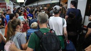 Un centenar de viajeros intenta subir a uno de los trenes de 'Rodalies'durante la huelga convocada por el sindicato CGT, esta mañana