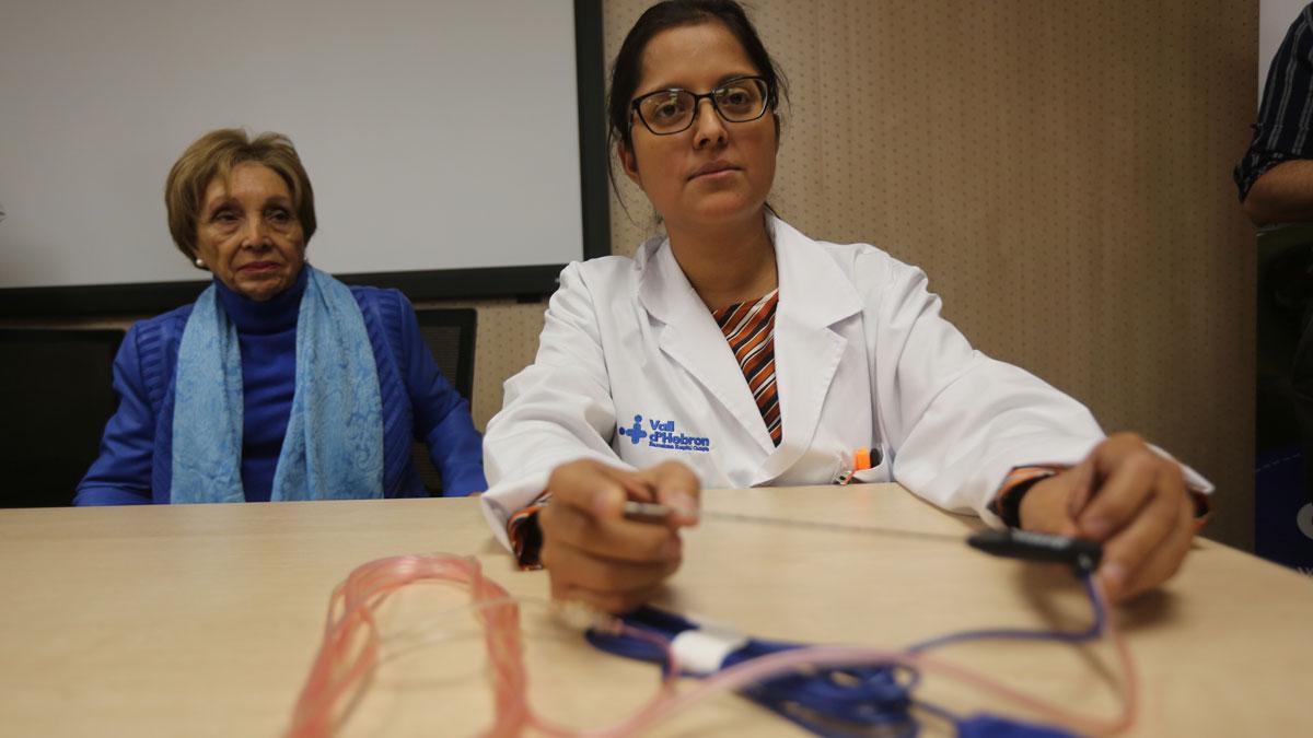 La doctora Elisabeth Pando (derecha) muestra la aguja que se utiliza para la radiofrecuencia intraoperatoria.A la izquierda, lapaciente María José. Ambas aparecen en el vídeo comentando la intervención.
