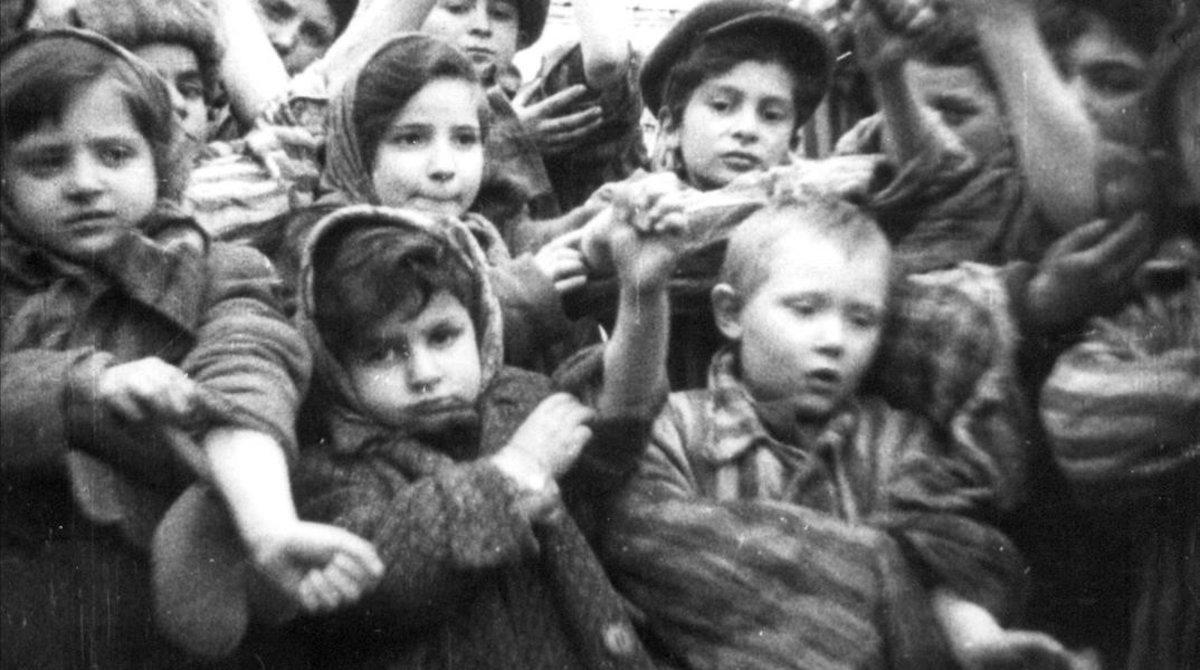 Algunos de los 600 niños que sobrevivieron a las penalidades del campo de concentración de Auschwitz-Birkenau muestran los números tatuados en sus brazos.
