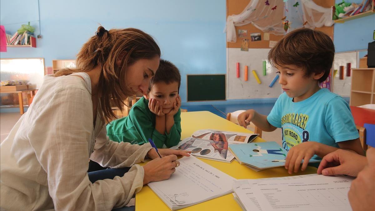 Una maestra conversa con dos niños en el aula de un colegio.