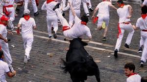 Un corredor es volteado por un toro en el primer encierro de San Fermín.
