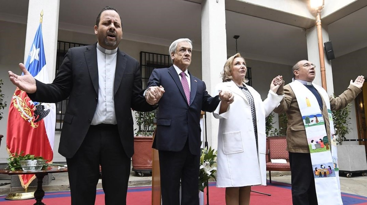 El presidente de Chile, Sebastián Piñera, (segundo por la izquierda)y su esposa,Cecilia Morel,rezan junto a dos religiosos en el acto conmemorativo del aniversario del golpe de Estado de 1973.