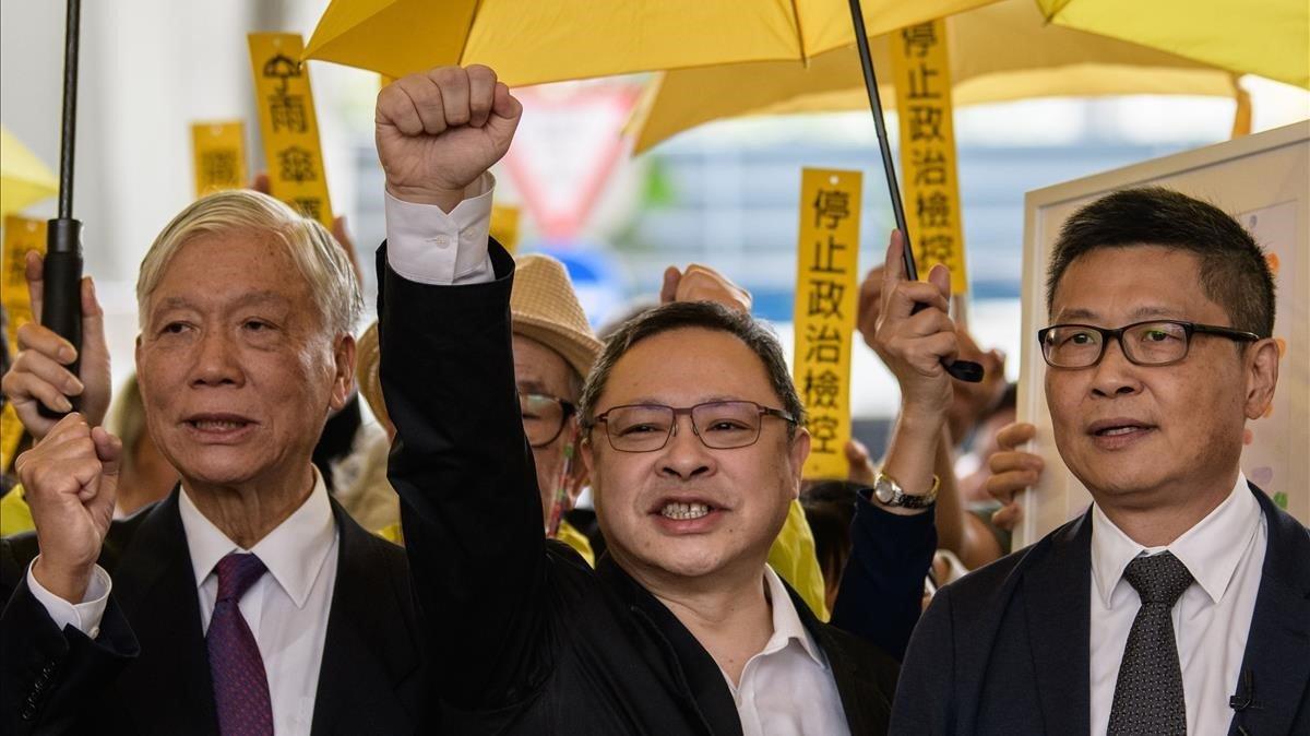 De izquieda a derecha, Chu Yiu-ming,Benny Tai yChan Kin-man, saludan a su seguidores antes de entrar en el tribunal deWest Kowloon enHong Kong.