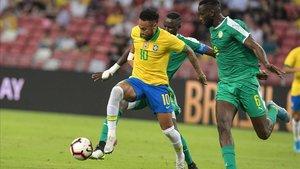 Neymar pugna conSané, durante el amistoso Brasil-Senegal en Singapur.
