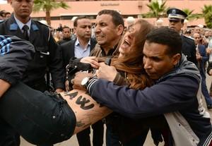 Policías de paisano arrestan a las activistas de Femen que se han desnudado ante un tribunal marroquí.