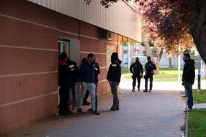 Agentes de los Mossos salen de uno de los edificios registrados, en el barrio de la Verneda.