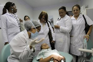 Cuban doctors observe a dental procedure during a a training session at a health clinic in BrasiliaBrazilCuba saidit is ending a program that sent government doctors to remote regions of Brazil in exchange for millions in badly needed dollars.AP Photo Eraldo PeresFile