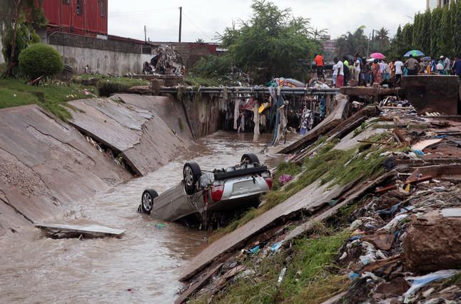 Un coche quemado tumbado en el agua cerca de la gasolinera que estalló en Ghana.