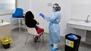 Un trabajador de un centro de atención primaria en Barcelona se prepara para hacer una prueba de coronavirus a un paciente.