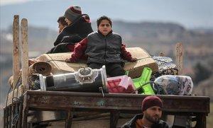 Desplazados sirios se sientan en la parte trasera de un camión con sus pertenencias huyendo de la ciudad de Idlib.