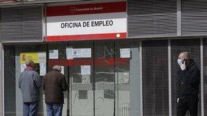 Dos personas leen los carteles de una oficina de empleo cerrada, el pasado lunes.