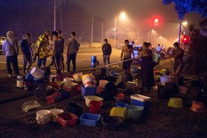 La gente lleva una manguera para ayudar a combatir un incendio en Vigo, el domingo.