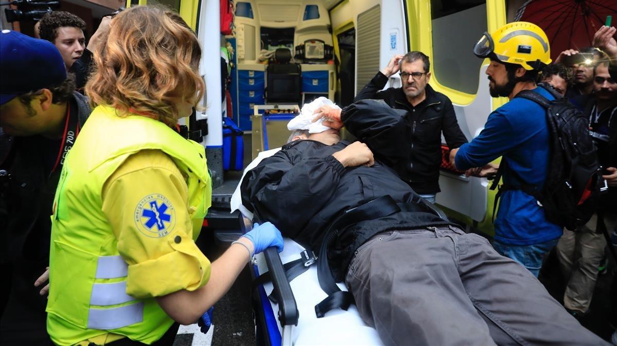 Roger Español es atendido por los servicios de emergencias tras ser herido por una pelota de goma durante la carga policial en la escuela Ramon Llull el 1-O.
