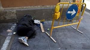 Un indigent dorm al mig del carrer a Barcelona.