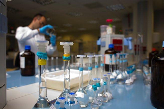 Un investigador vertiendo líquido de un vaso a una probeta en un laboratorio en Barcelona