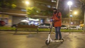 Un joven conduce su patinete por la Rambla del Carme de Esplugues de Llobregat.