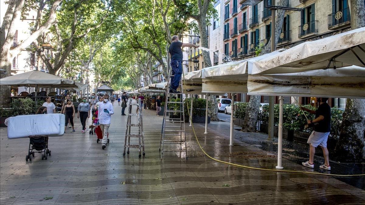 Las terrazas de Las Ramblas se desperezaban, el pasado 22 de mayo, para estar presentables para el público local en la fase 1 de la desescalada, a la espera de que llegue su cliente favorito.