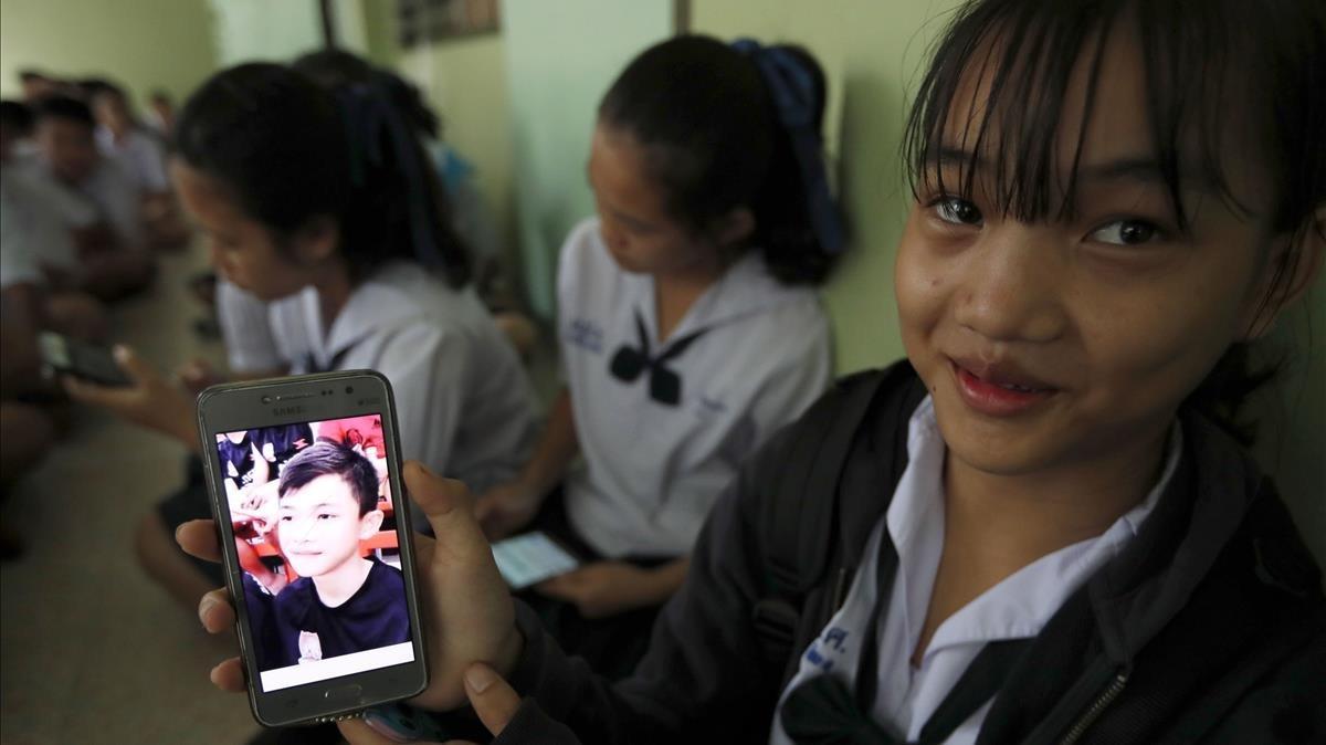 Una estudiante tailandesa muestra una fotografia de su companero de clase, Duangpetch Promthep, uno de los niños rescatados de la cueva deMae Sai.