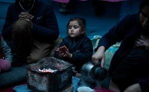 Marjan Hosini, de 3 años, calienta sus manos sobre el carbón caliente en su refugio temporal en un asentamiento improvisado junto al campamento de Moria, en Lesbos.