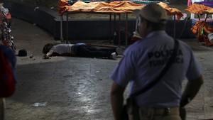 Un policía frente a un hombre asesinado en Acapulco.