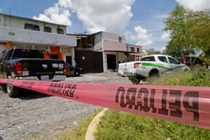 Oficiales de policía resguardan la zona por un asesinato múltiple en México.
