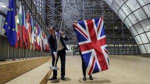 Unos trabajadores retiran la bandera británica de la sede del Consejo Europeo enBruselas.